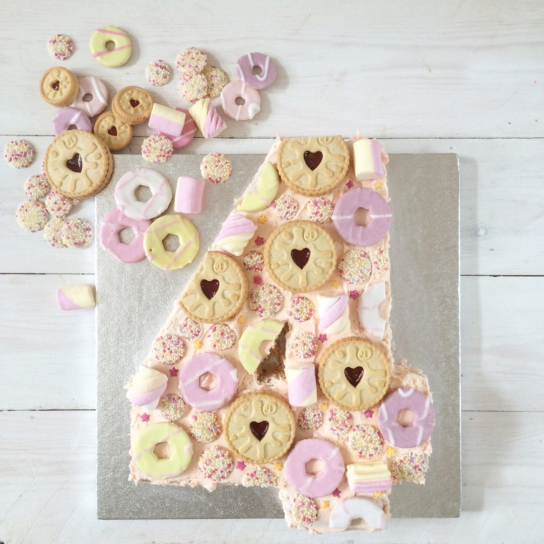Pink number 4 cake with strawberry milkshake icing and topping with biscuits