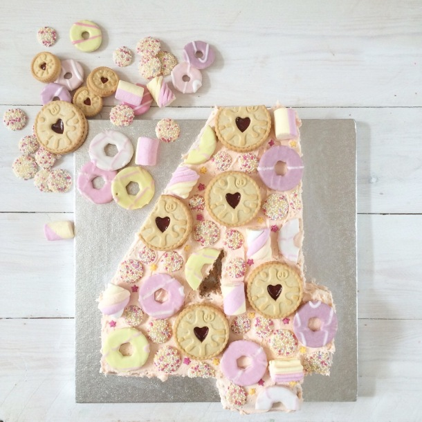 Pink number 4 cake with strawberry milkshake buttercream icing and topped with jammy dodger biscuits, party rings, marshmallows and jazzies